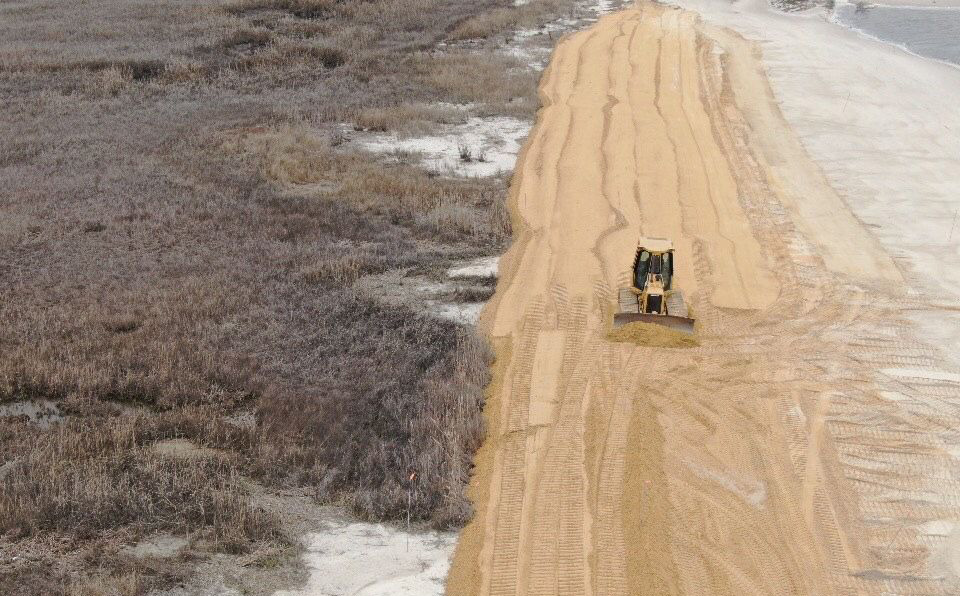 Backhoe spreading sand across the beach as part of restoration efforts at Cooks Beach, NJ